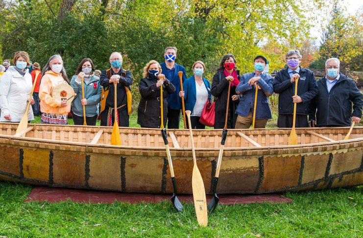 Speakers at The Canadian Canoe Museum's construction commencement event on October 16, 2021 in front of a 26-foot long birchbark canoe built by Métis elder Marcel Labelle: Chief Laurie Carr, Janet McCue, Chief Emily Whetung, Marcel Labelle, Minister Lisa MacLeod, MPP Dave Smith, Carolyn Hyslop, Victoria Grant, Jeremy Ward, Warden J. Murray Jones, and Councilor Andy Dufrane. (Photo: FusionRiver Photography courtesy of The Canadian Canoe Museum)