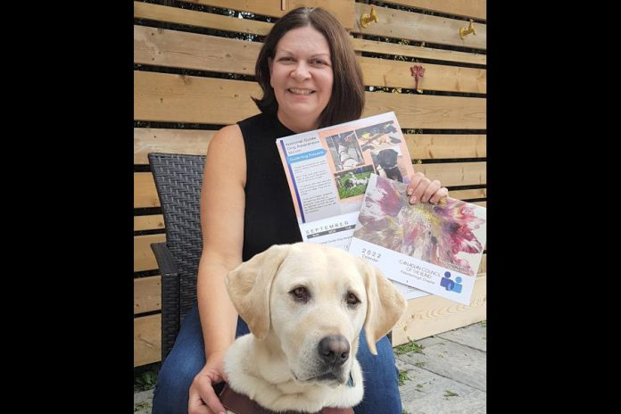 Leslie Yee, chair of the Canadian Council of the Blind's Peterborough chapter, with her guide dog Akira, displays the organization's 2022 fundraising calendar featuring cover art by Peterborough artist Lynda Todd. (Supplied photo)