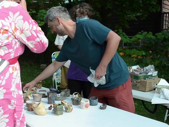 """John Marris during """"Fire Shift"""" from May to July 2021, a collaboration between local youth and Peterborough artists to make ceramic work and then experience a traditional outdoor pit firing process, part of Artsweek Shift2. (kawarthaNOW screenshot from Artsweek video)"""